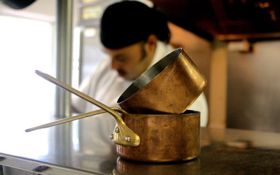 Chef behind copper pots